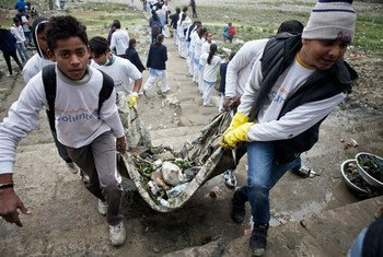 Young volunteers clean garbage from the Yamuna River banks in India.