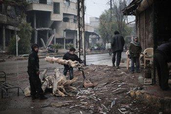 Deux enfants récupèrent des branches pour faire du feu dans le village de Kafar Batna, dans le Grand Damas, en Syrie.