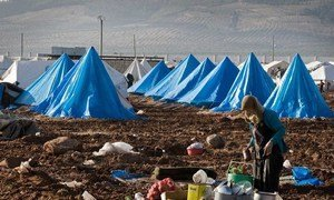 A woman prepares a meal at a makeshift outdoor cooking area, atop the muddy grounds of the Bab Al Salame camp for IDPs, near the border with Turkey in Aleppo Governorate, Syria (January 2014).