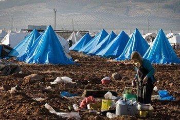 Una mujer siria cocina en un campamento de desplazados sirios cerca de la frontera con Turquía. Foto de archivo: UNOCHA