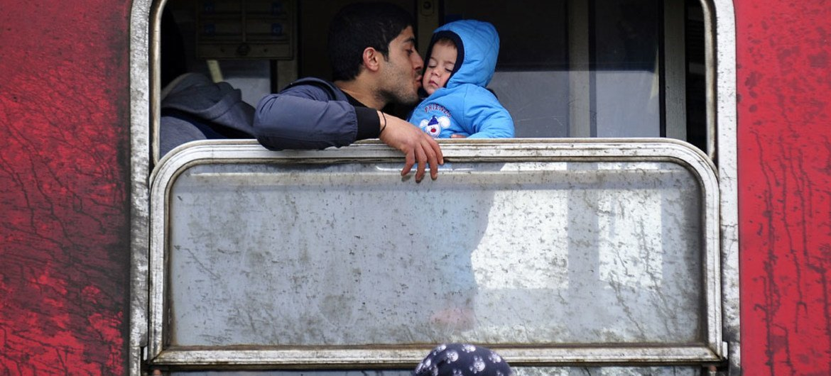 A father kisses his baby boy inside a train outside Vinojug transit center, near the town of Gevgelija, in the Former Yugoslav Republic of Macedonia.
