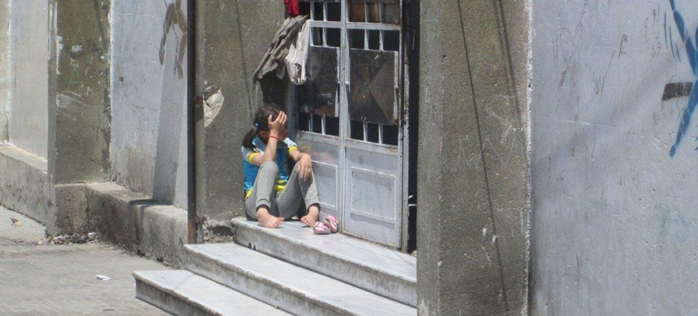 Una niña siria mira la calle desde la puerta de un albergue para desplazados en la ciudad de Alepo. Foto: UNICEF