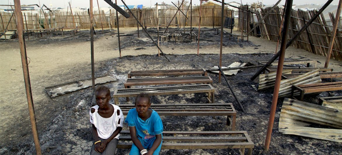 In South Sudan, Chubat (right), 12, sits with her friend in the burned ruins of her UNICEF supported primary school in Malakal Protection of Civilian site, which was burnt down in fighting on 17-18 February 2016.