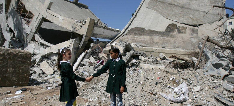 Школьницы у разрушенного в 2014  году здания школы в Газе.