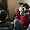 Children watching a virtual reality film in a refugee camp. Screen shot from UNTV 21st Century's Virtual Reality: Creating Humanitarian Empathy