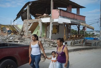 On 5 May 2016, two women and a young girl walk past a building destroyed by the earthquake in Nuevo Pedernales, Manabi, Ecuador.