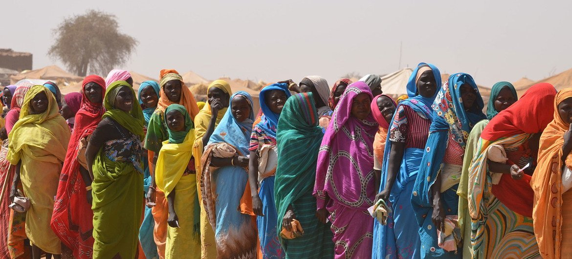 Women carry empty bags as they line up to receive food at the Tawilla site for newly arrived IDPs from Jebel Marra, South Sudan. 22 February 2016.