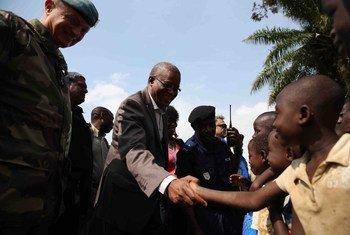Le Représentant spécial et chef de la Mission de stabilisation des Nations Unies en République démocratique du Congo (MONUSCO), Maman Sidikou (centre), salue des enfants à Oicha, dans le Nord-Kivu.