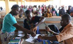 Making cash transfer payments to women in Freetown, Sierra Leone.