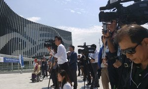 Media gather at the Gyeongju Hwabaek International Convention Center for a flag raising ceremony prior to the 66th DPI/NGO Conference. 29 May 2016.