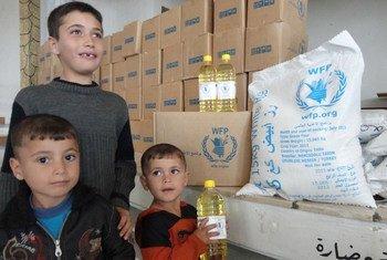 Семья   сирийских беженцев из сирийского города Дарая   получила продовольственный паек. Фото ВПП/Х.Алсалех