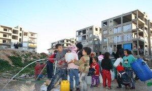 Children collect water at the Al-Riad shelter, Aleppo, Syria.