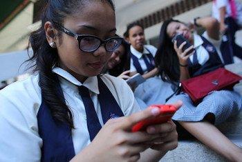 Una estudiante Filipina mira su teléfono inteligente.