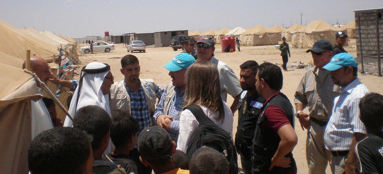 Interação entre trabalhadores humanitários e recém-deslocados de Fallujah no campo iraquiano de Amiriyat Al Fallujah.