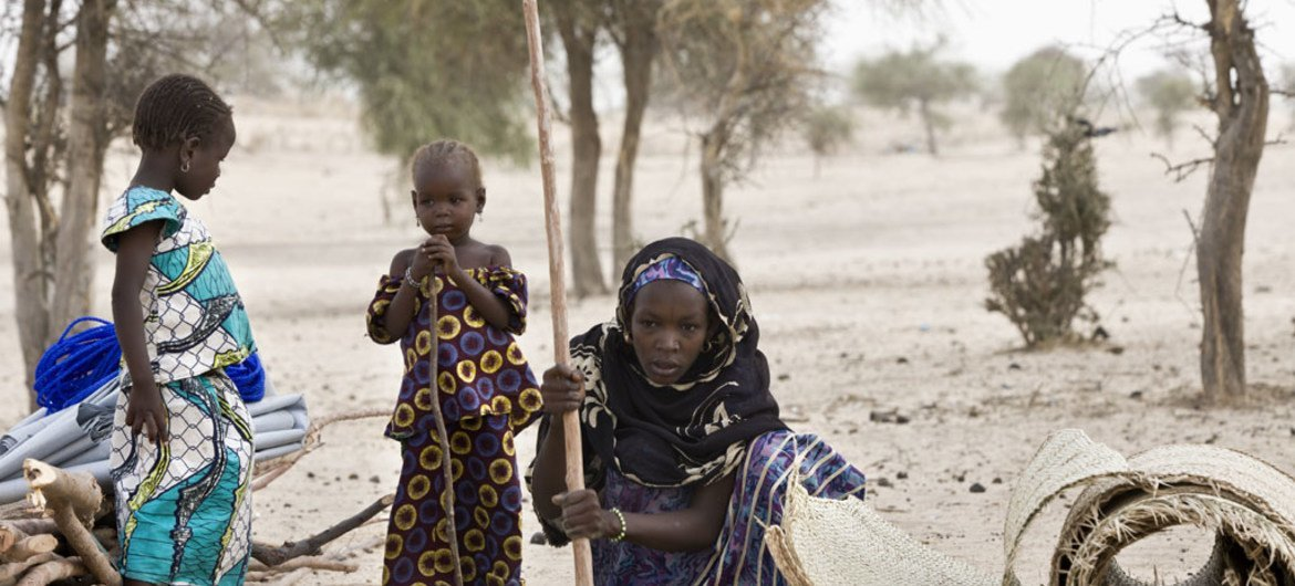 Nigerian refugee Boussam installs a pole to start building a shelter in Sayam Forage camp, in Niger's Diffa region.