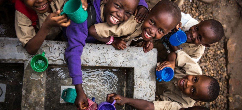 Watoto wajaza vikombe maji kwenye bomba la maji lililojengwa na UNICEF katika shule ya msingi huko Bujumbura, Burundi.