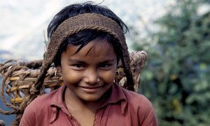 In Nepal, a young girl transports agricultural goods along a 65 km mountain path. When children engage in work that is not appropriate for their age, this is child labour.