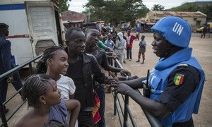 Senegalese peacekeepers from the UN Multidimensional Integrated Stabilization Mission in Mali (MINUSMA) Formed Police Unit (FPU) speak with Malians while they patrol outside Mamadou Konate Stadium during an event to promote peace among the youth.