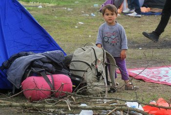 An Afghan child showing all his family's belongings in front of their tent near Röszke, Hungary.