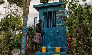 A woman along with her son, fills her containers at a water distribution point in Las Palmas, Haiti. Logan Abassi/UN/MINUSTAH