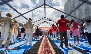 Des participants pratiquent le yoga lors de la célébration de la Journée internationale du yoga à l'ONU en 2015. Photo ONU/Mark Garten
