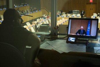 El intérprete de la ONU Nicolás Diaz realiza una traducción simultánea al español de las palabras del enviado especial de la ONU para Siria, Staffan de Mistura (en pantalla), en la Asamblea General de la ONU. Foto: ONU/Mark Garten