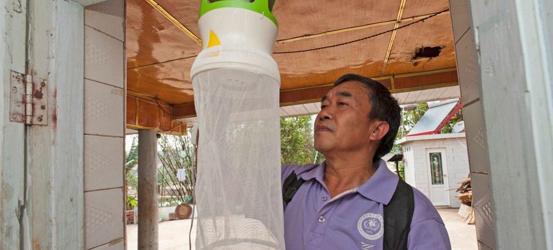 为防止寨卡病毒的传播,一名卫生工作者正在检查防蚊装置的安装。  图片:WHO/TDR/S. Lim