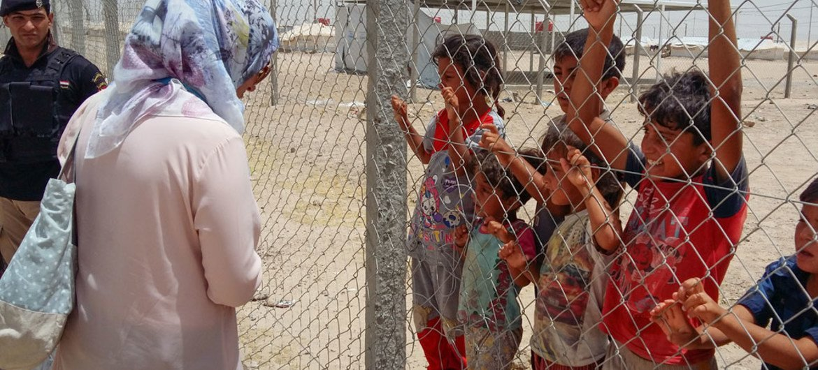 In Iraq, a UNICEF child protection staff member speaks to children who are staying in the Amiriyat Al Fallujah IDP camp in the province of Anbar that has been established for internally displaced persons fleeing conflict in Fallujah.