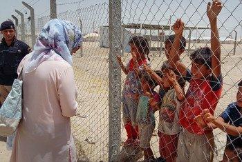 En Iraq, un membre de l'UNICEF parle à des enfants dans un camp pour personnes déplacées ayant fui le conflit à Falloujah, dans la province d'Al-Anbar. Photo : UNICEF / Overtoun Mgemezulu