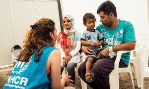 Ghulam Ali Jaffari, sa famme Nabila, et leur fils de 2 ans Amir parlent avec une employée du HCR en attendant de récupérer leur document d'identité du Service grec d'asile. Photo HCR/Achilleas Zavallis