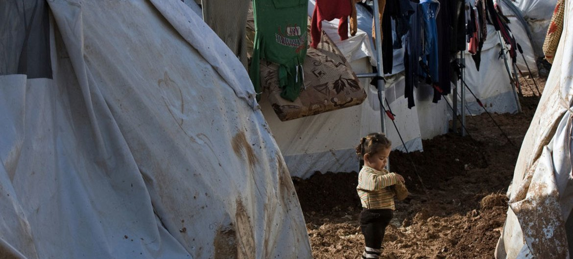 A girl stands barefoot on a muddy walkway between rows of tent shelters, in the Bab Al Salame camp for internally displaced persons, near the border with Turkey, in Aleppo Governorate, Syria.