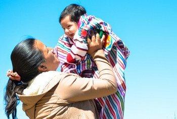 Una mujer peruana sujeta a su bebé.