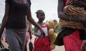 Une jeune réfugiée et sa famille traversent la frontière entre le Soudan du Sud et l'Ouganda. Photo : UNHCR / Will Swanson