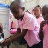 一群海地儿童正在学习怎样正确地洗手,以预防霍乱。