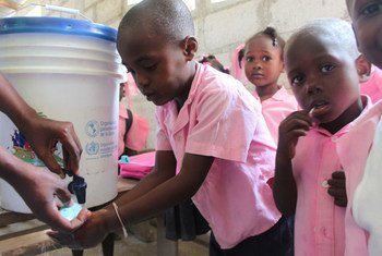 A group of Haitian children learn how to properly wash their hands in an effort to raise awareness about cholera prevention.