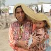 Mãe cobre o filho para o proteger do calor em Sindh, no Paquistão.