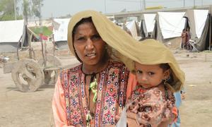In Sindh province, Pakistan, a mother tries to shield her four-year-old daughter from scorching heat.