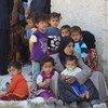Une femme et ses enfants attendent devant un centre médical dans le village d'Al-Radwanieh, dans la zone rurale d'Alep, en Syrie.