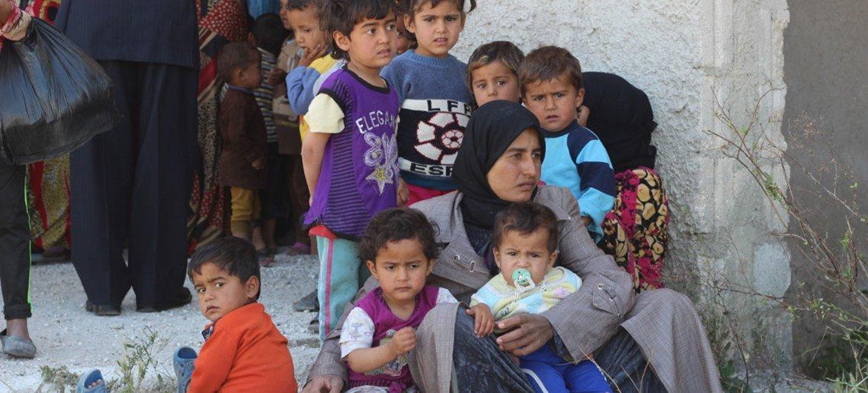 A woman and children wait outside a medical centre in Al-Radwanieh village, rural Aleppo, Syria.