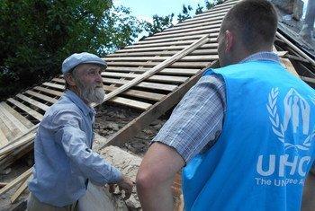 乌克兰东部一位老人在与难民署工作人员交谈。难民署图片/Daria Volkova