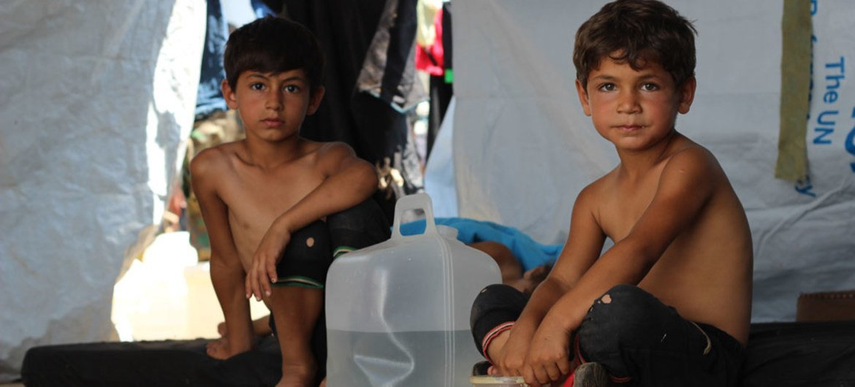 طفلان سوريان في خيمة مؤقتة على الطريق السريع في الجزء الغربي من مدينة حلب، سوريا