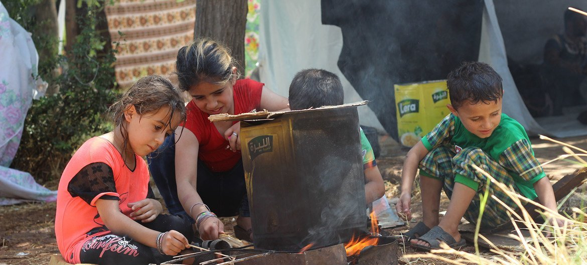 In the Syrian Arab Republic, an extended family takes shelter under a makeshift tent on the sidewalk after the latest wave of attacks.. The grandfather is wheelchair-bound. The children prepare a fire for cooking and hang out clothes to dry.