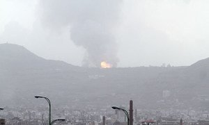 A large ball of fire and plume of smoke – resulting from an air strike that hit a military site on Faj Attan Mountain, Yemen, high above Sana'a, the capital – rises skyward and begins to spread over the city below.