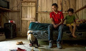 Alexis, 18, with his brother Wilson, 6, and their pet, a Caracara, at home in Omoa, Honduras.