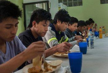 Jóvenes centroamericanos almorzando en un albergue de UNICEF.