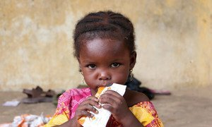 After fleeing Boko Haram violence, a child, at Dalori 2, a displaced people's camp located on the outskirts of Maiduguri, Nigeria, eats Plumpy'sup, a ready-to-use, highly nutritious food to combat malnutrition.