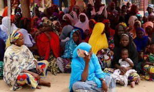 In northeastern Nigeria, people who fled Boko Haram violence, gather at a mobile phone-based cash distribution site set up by WFP and the Government in Maiduguri.