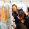 叙利亚难民儿童在国际移民组织的官员指导下了解美国地图。
