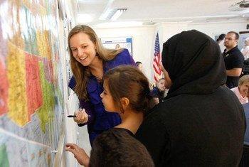 Девочка из числа сирийских беженцев в Иордании  изучает карту США. Фото МОМ