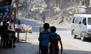 On 24 August 2016, two children walk arm in arm down a war damaged street in Aleppo, Syria.